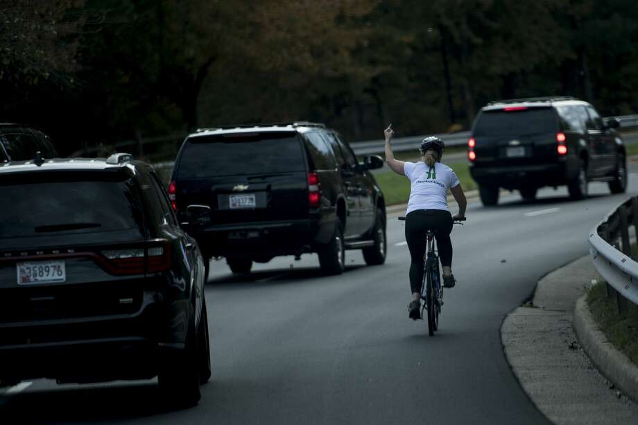 Juli Briskman gestures with her middle finger as a motorcade with US President Donald Trump departs Trump National Golf Course October 28, 2017 in Sterling, Virginia. Photo: Brendan Smialowski / AFP / Getty Images