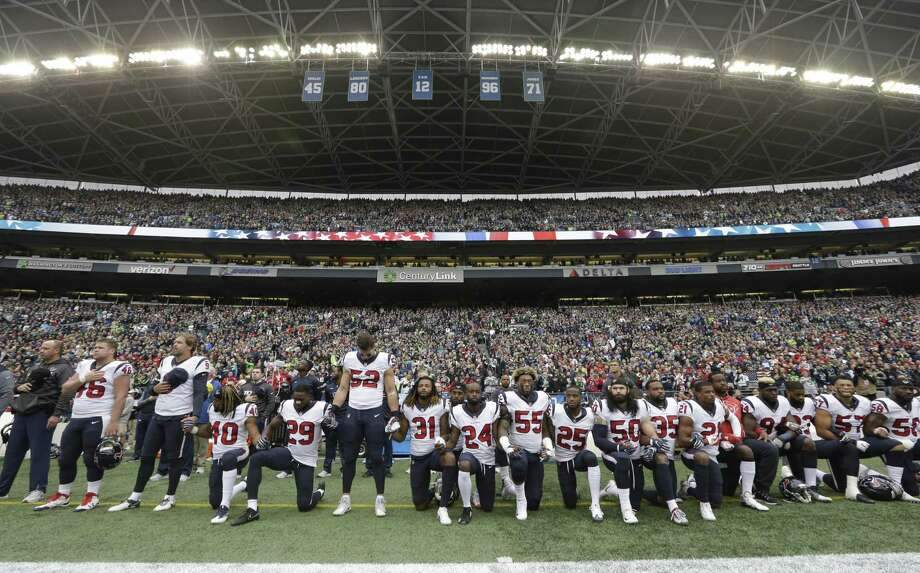 Houston Texans players kneel and stand during the singing of the national anthem before an NFL football game against the Seattle Seahawks, Sunday, Oct. 29, 2017, in Seattle. (AP Photo/Elaine Thompson) Photo: Elaine Thompson, STF / Associated Press / Copyright 2017 The Associated Press. All rights reserved.