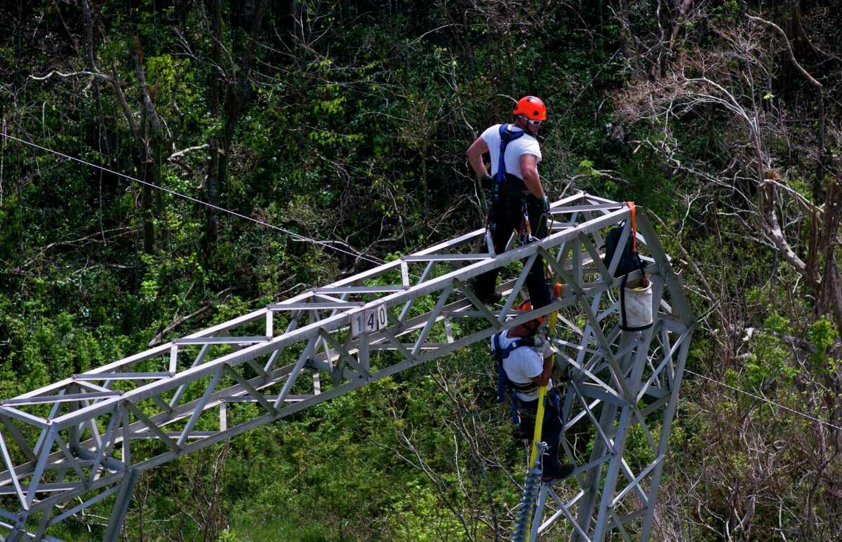 In this Oct. 15, 2017, file photo, Whitefish Energy Holdings workers restore power lines damaged by Hurricane Maria in Barceloneta, Puerto Rico. HPD police officers are leaving Thursday to go assist Puerto Rican police.