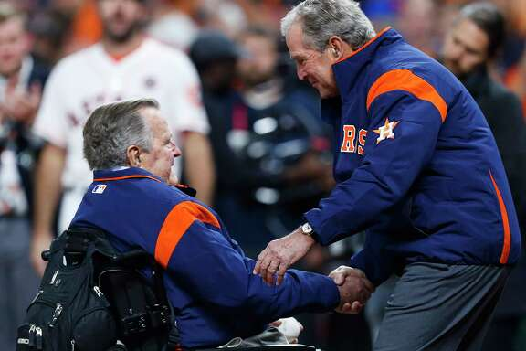 Former President George H.W. Bush and his son, former President George W. Bush, throw out the first pitch of Game 5 of the World Series to at Minute Maid Park on Sunday, Oct. 29, 2017, in Houston.
