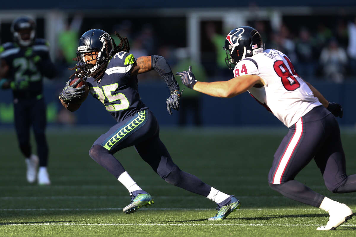 Seahawks corner back Richard Sherman avoids Texans tight end Ryan Griffin while returning an interception during the second half of an NFL game at CenturyLink Field on Sunday, Oct. 29, 2017.