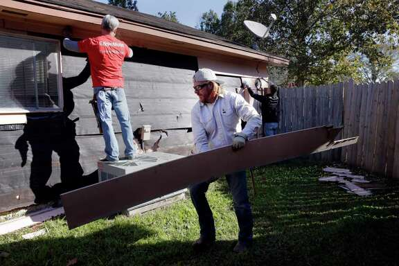 Mike Shot, left, an ExxonMobil volunteer with Rebuilding Together Houston, and Chip Gaines repair Doris Davis' home.