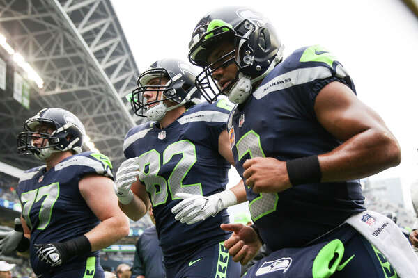 Seahawks quarterback Russell Wilson, tight end Luke Willson, and offensive lineman Ethan Pocic head back into the locker room before playing the Texans at CenturyLink Field on Sunday, Oct. 29, 2017.
