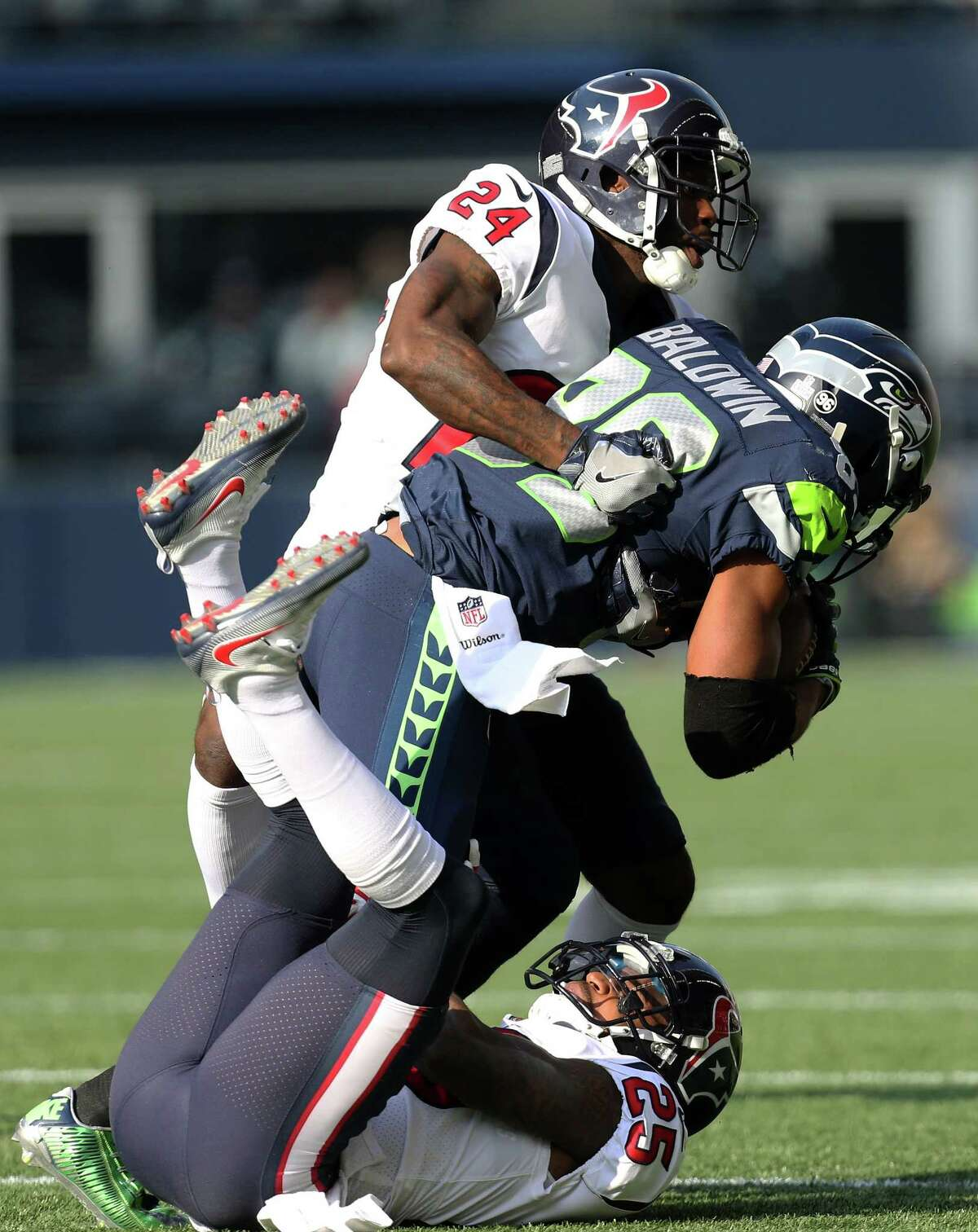 Houston Texans cornerbacks Johnathan Joseph (24) and Kareem Jackson (25) tackle Seattle Seahawks wide receiver Doug Baldwin (89) during the first half of the game at CenturyLink Field Sunday, Oct. 29, 2017, in Seattle. The Seahawks won 41-38.