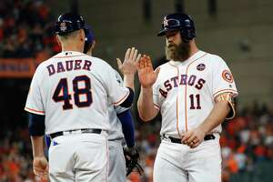 Houston Astros catcher Evan Gattis (11) celebrates with first base coach Rich Dauer (48) after hitting a single during the third inning of Game 5 of the World Series at Minute Maid Park on Sunday, Oct. 29, 2017, in Houston.