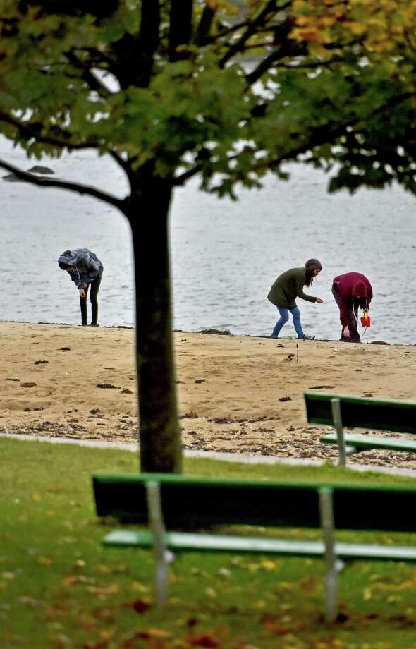Robert Lombard, 20, of Branford, left, with friend Zoe Marchand, 19 of Danbury, center, assist his sister Morgan Lombard, 18, right, collecting sea glass in the rain Sunday afternoon at the Parker Memorial Park Branford Point beach for Morgan's jewelry online business, FairyShop Treasures at Etsy.com. The shoreline experienced strong winds, power outages and some flooded streets later Sunday. Photo: Peter Hvizdak / Hearst Connecticut Media / New Haven Register