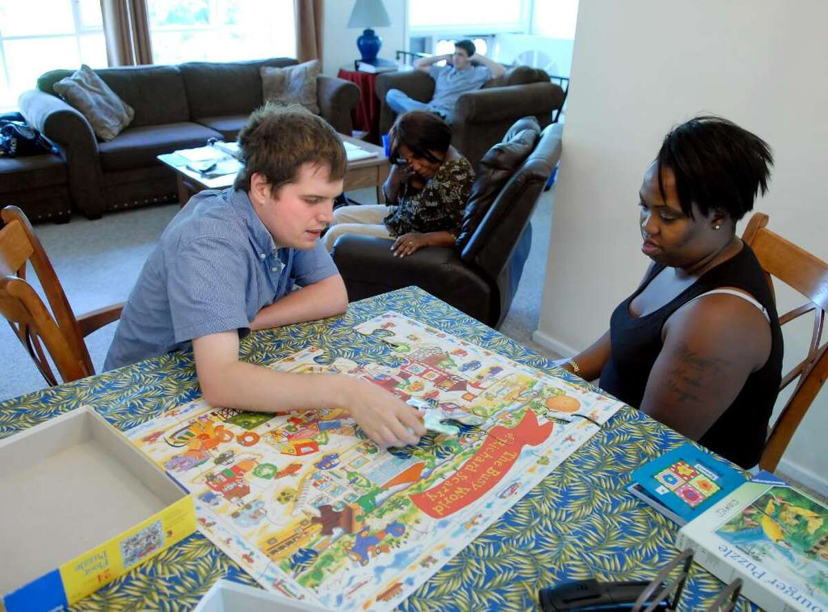 Sean Stuart, 24, left, puts a puzzle together with Abilis program manager Gillian Graham, right, at an Abilis group home in Cos Cob, Friday afternoon, June 25, 2010. Stuart is autistic and a resident at the home.