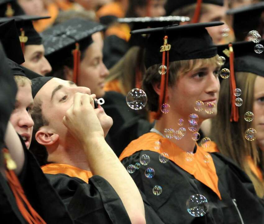 Ridgefield High School graduates blow bubbles while they wait for their turn to get their diplomas at the Western Connecticut State University O'Neill Center on Friday June 25, 2010 during their commencement ceremony. From left, Steven Montanari, John Morrison and Duncan Morrissey.