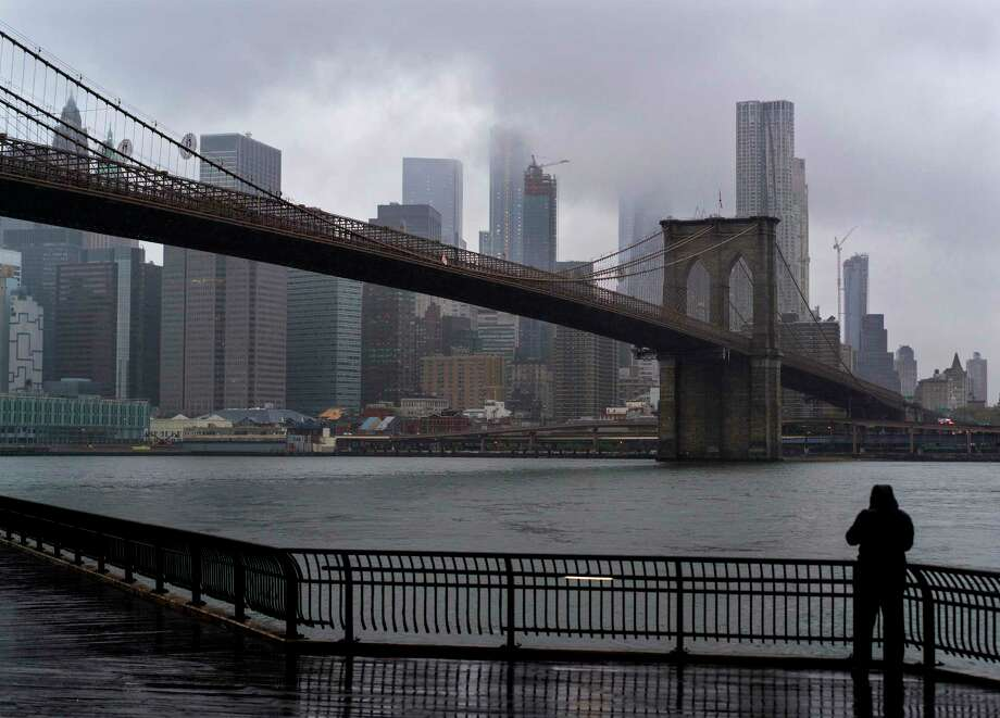 FILE -- A person on the Brooklyn side of the East River faces the rain and clouds as they loom over lower Manhattan on Sunday, Oct. 29, 2017, in New York. A tour helicopter reportedly crashed into the East River Sunday evening, according to witnesses. Photo: Craig Ruttle / FR61802 AP