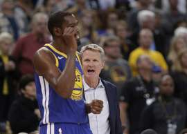 Head coach Steve Kerr talks with Kevin Durant (35) in the fourth quarter as the Golden State Warriors played the Detroit Pistons at Oracle Arena in Oakland, Calif., Sunday, October 29, 2017. The Pistons defeated the Warriors 115-107.