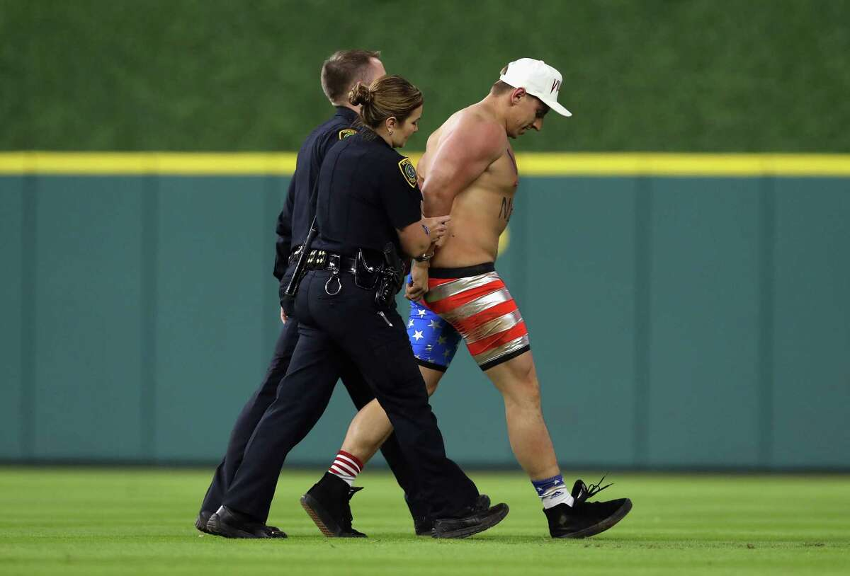 HOUSTON, TX - OCTOBER 29: Security apprehends a fan running on the field during game five of the 2017 World Series between the Houston Astros and the Los Angeles Dodgers at Minute Maid Park on October 29, 2017 in Houston, Texas.