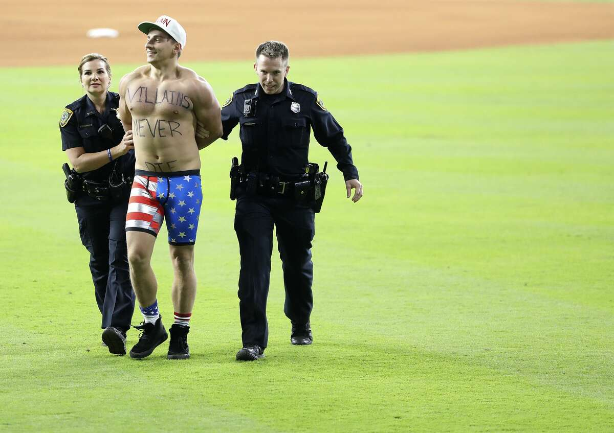 A spectator is removed from the field by security during the World Series on Sunday, Oct. 29, 2017, in Houston.