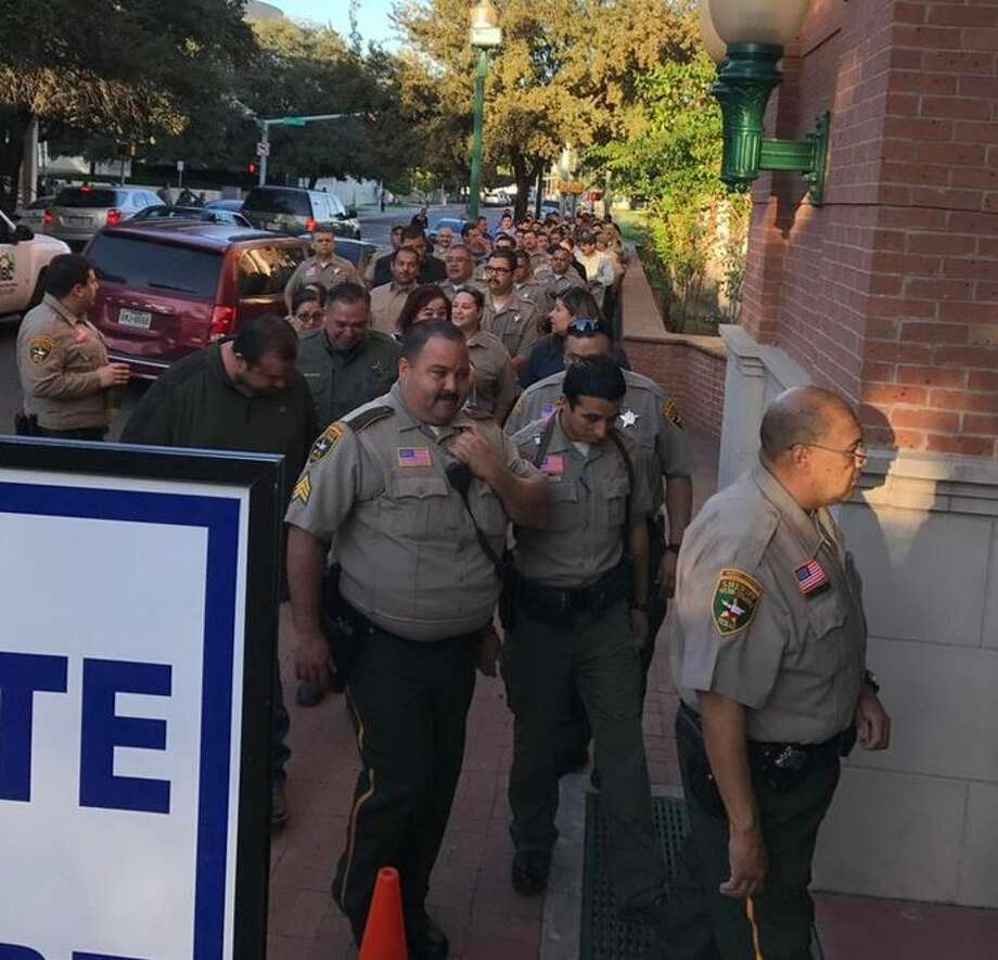 A line of Webb County Sheriff's Office deputies head to the polls during early voting at the Billy Hall Administration Building.  Photo: Julia Wallace/Laredo Morning Times
