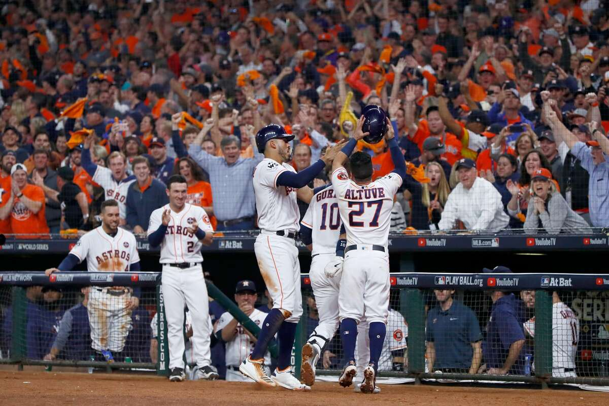 Yuli Gurriel #10 of the Houston Astros celebrates with Carlos Correa #1 and Jose Altuve #27 after hitting a three run home run during the fourth inning against the Los Angeles Dodgers in game five of the 2017 World Series at Minute Maid Park on October 29, 2017 in Houston, Texas.