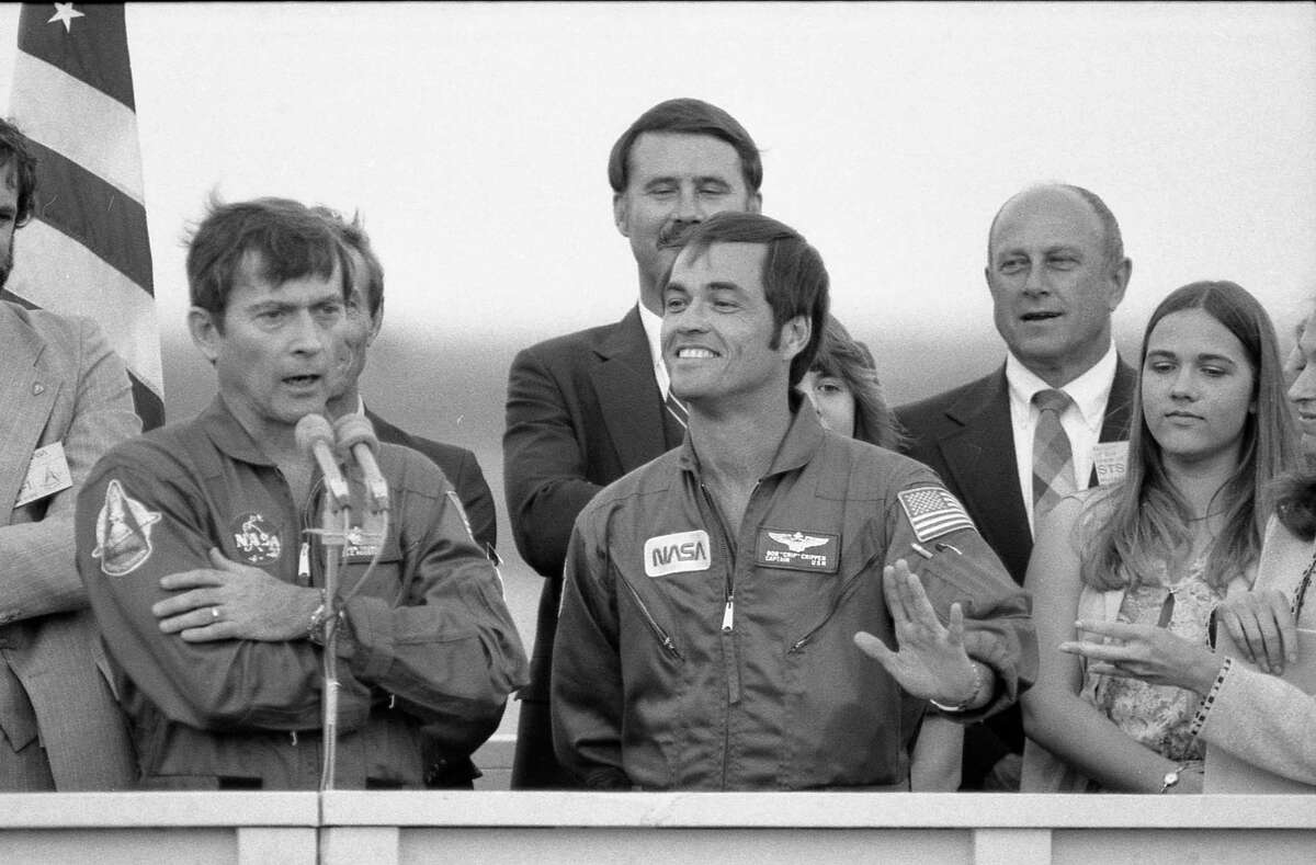 Space shuttle mission STS-1 astronauts John Young, at microphone, and Robert Crippen waving from podium at Ellington AFB ceremonies for their return to Houston following their space shuttle landing at Edwards AFB in California in 1981.