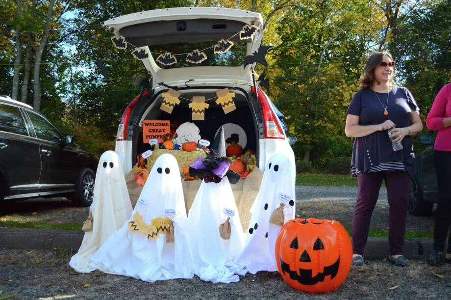 Photo: Jarret Liotta / For Hearst Connecticut Media / Cindy Glover of Fairfield stand by her Charlie Brown-themed display at the 2nd annual Trunk or Treat tailgate Halloween event at