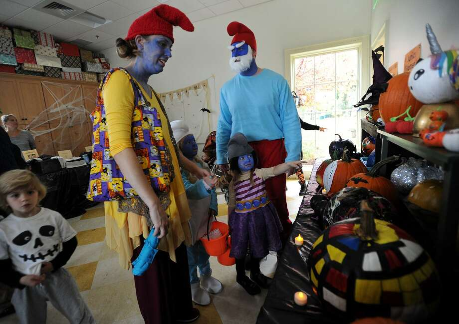 Dressed as a family of smurfs, Keri and Brian Stedman of Westport, and their daughters Kassia, 5, and Avery, 4, attend the annual Halloween on the Green at the Fairfield Museum & History Center on Sunday, October 29, 2017. The popular event was moved inside because of the rain. Photo: Brian A. Pounds / Hearst Connecticut Media / Connecticut Post