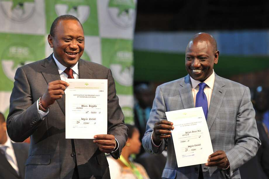 Kenyan President Uhuru Kenyatta (left) and his running mate, William Ruto, hold certificates of election in Nairobi after a national election panel certified their victory in a rerun vote. Photo: TONY KARUMBA, AFP/Getty Images
