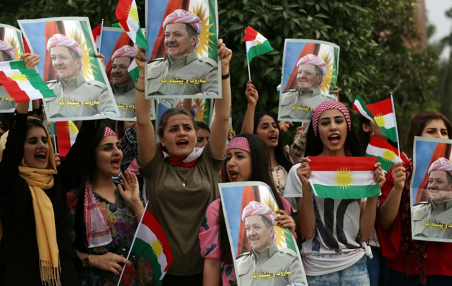 Students at Salahaddin University in Irbil, Iraq, hold posters showing their support for Kurdish leader Masoud Barzani. Barzani has decided to step down and not seek re-election. Photo: SAFIN HAMED, AFP/Getty Images