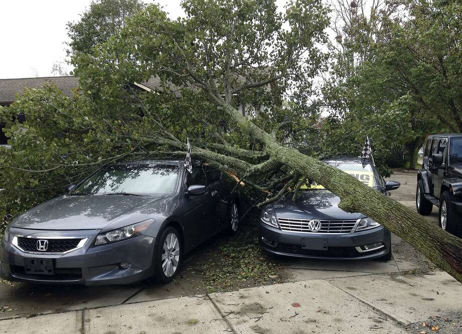 A toppled tree covers cars for sale at a dealership in Warwick, R.I. Falling trees knocked down power lines across the Northeast, and it could take days to restore electricity to customers. Photo: Jennifer McDermott, Associated Press