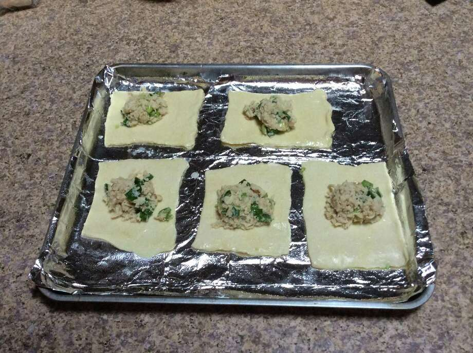 Chicken mixture is placed on the puff pastry square. Photo: Stephen Fries