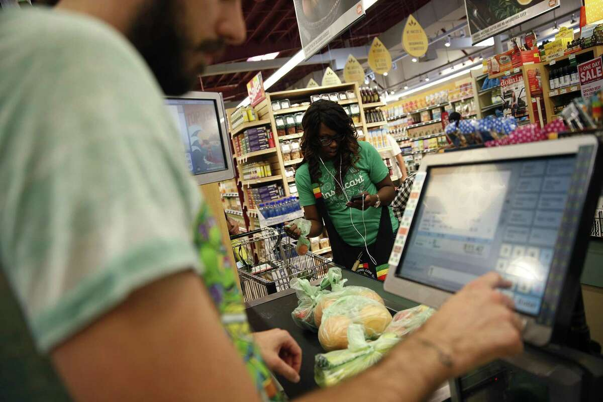 """A Whole Foods cashier rings up groceries in Sherman Oaks, Calif. Whole Foods announced plans to hire some 6,000 people starting Thursday, Nov. 2, 2017, which it proclaimed a """"national hiring day"""" under new parent Amazon. (Robert Gauthier/Los Angeles Times/MCT)"""