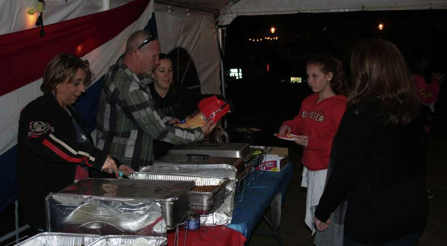 Theresa McCulloch (left), Charles Hay (second from left) and Marcia Hay (third from left) serve up barbecue plates to a couple of visitors at the Bad to the Bone Motorcycle Shop's 10th anniversary celebration held on Oct. 28. Photo: Jacob McAdams