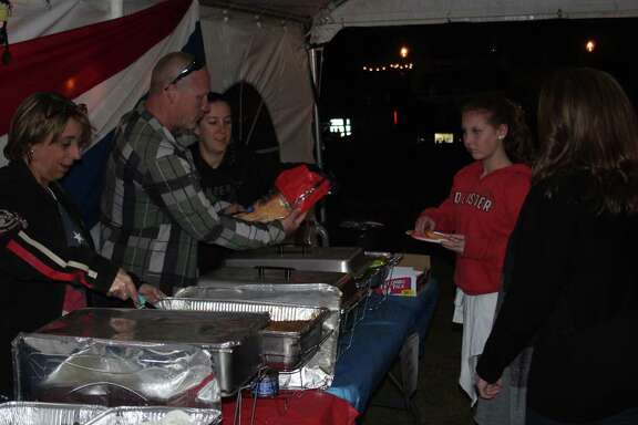 Theresa McCulloch (left), Charles Hay (second from left) and Marcia Hay (third from left) serve up barbecue plates to a couple of visitors at the Bad to the Bone Motorcycle Shop's 10th anniversary celebration held on Oct. 28.