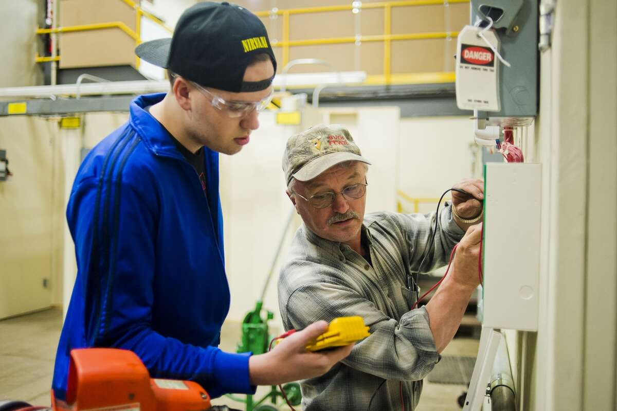 Sid Render of Coleman, right, instructs Leif Carlson of Midland, 18, during an electrical course provided by the Associated Builders and Contractors Greater Michigan Chapter on Thursday, Oct. 26, 2017 in Midland. (Katy Kildee/kkildee@mdn.net)