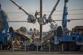 SANTA ROSA, CA -OCTOBER 14: Pacific Gas and Electric Company crews work to restore power near fire-damaged Cardinal Newman High School on October 14, 2017 in Santa Rosa, California. At least 32 people are confirmed dead with hundreds still missing. Officials expect the death toll to rise, and now estimate that 5,700 structures have been destroyed. (Photo by David McNew/Getty Images)