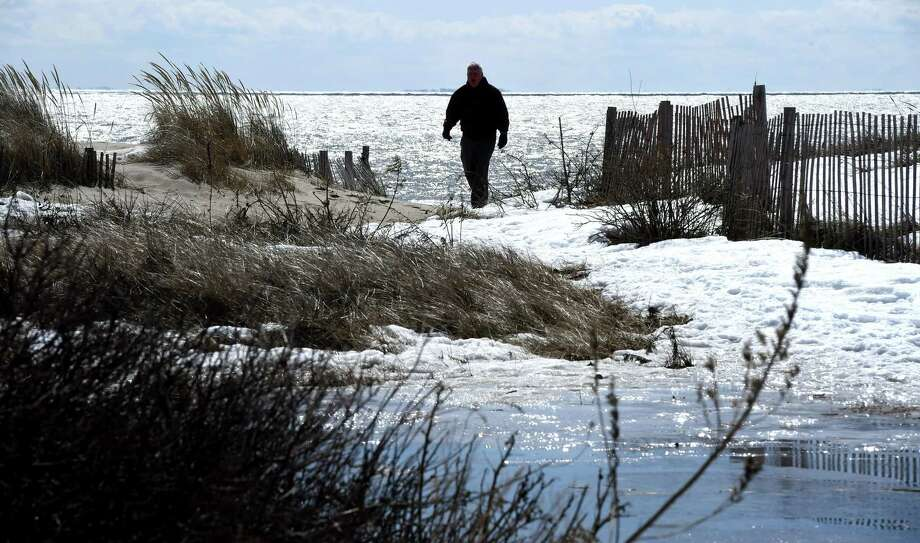 (Arnold Gold-New Haven Register)  Bob Phoenix of Essex cuts his walk short because of the wind and ice at Hammonasset Beach State Park's West Beach in Madison on 3/18/2015.