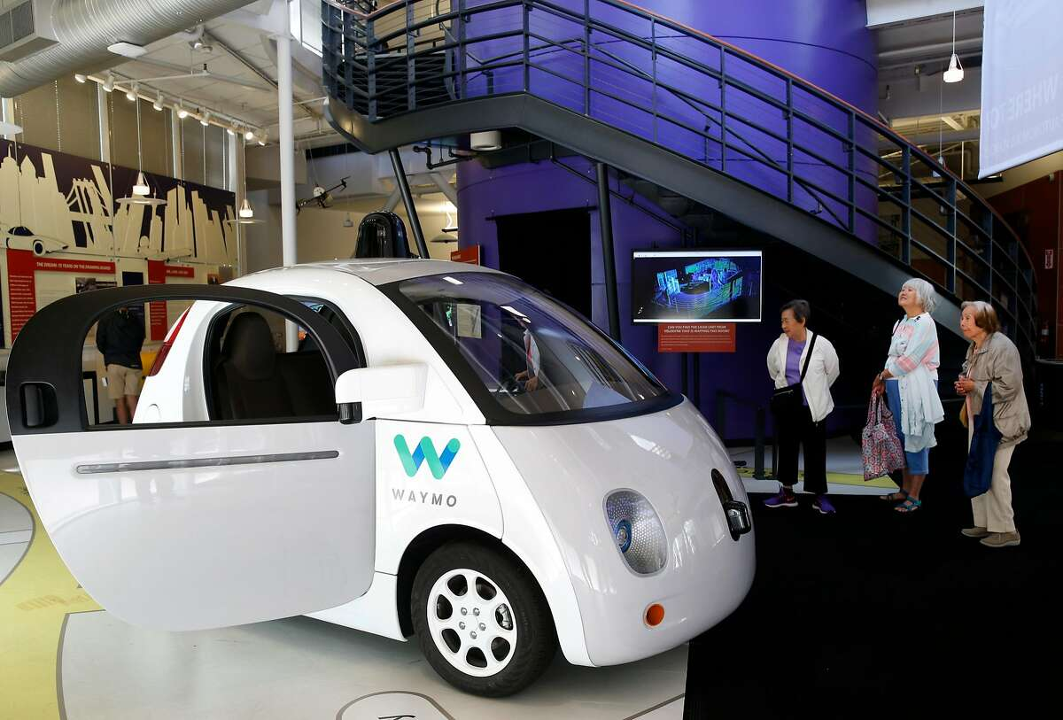Visitors view a Waymo self-driving car displayed at the Computer History Museum in Mountain View, Calif. on Wednesday, July 12, 2017.