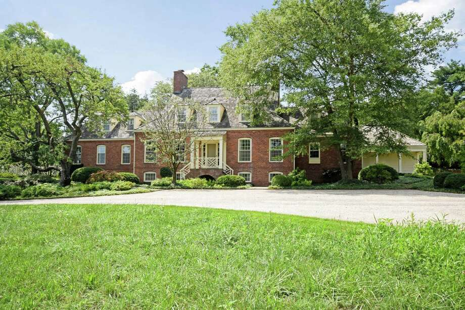 The red brick Tidewater colonial house at 16 Wrenfield Lane sits high on a hill on a property of almost two acres, and features a butterfly staircase on its front facade.