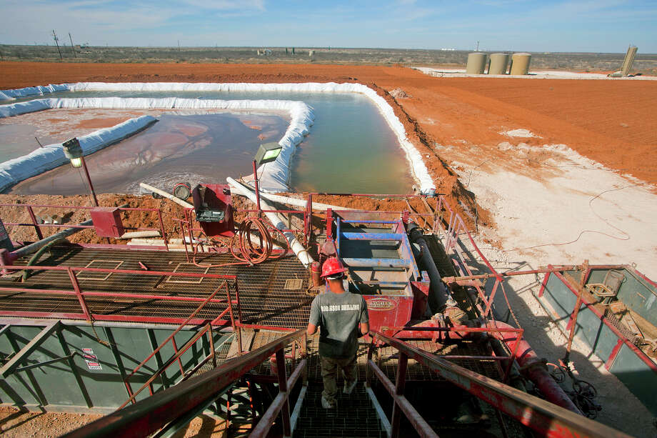 Chance Lang descends toward the water pool attached to Robinson Drilling rig #4 in Midland County. Photo:  James Durbin/Reporter-Telegram