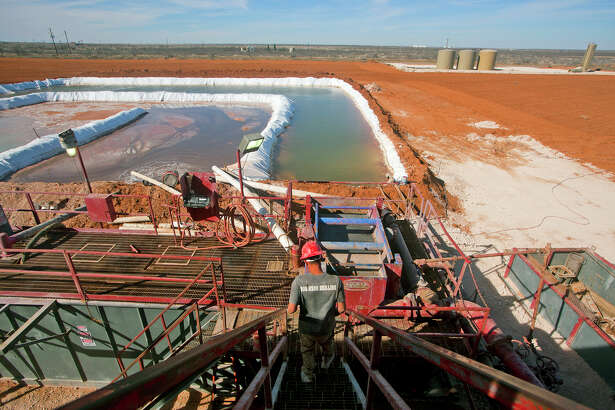 Chance Lang descends toward the water pool attached to Robinson Drilling rig #4 in Midland County.