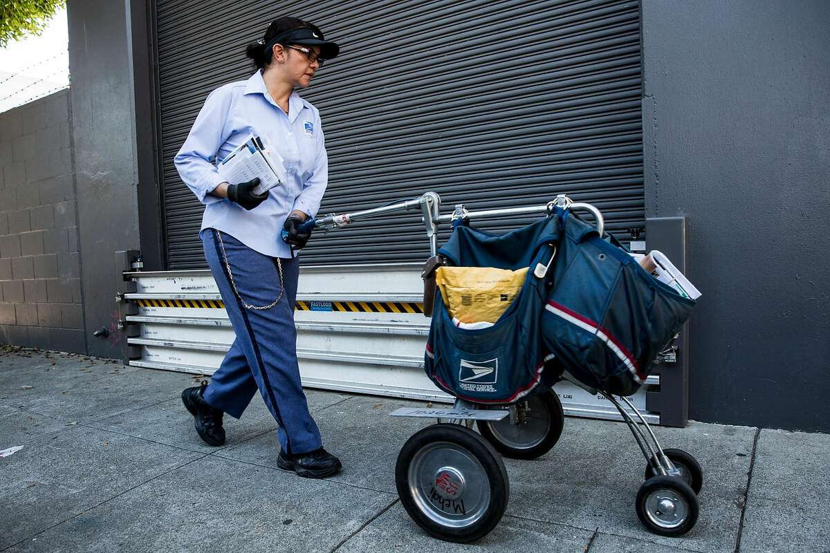 A United States Postal Service worker pushes a mail cart past a floodwall on Treat Ave in the Mission District of San Francisco, Calif. on Friday, Oct. 27, 2017.