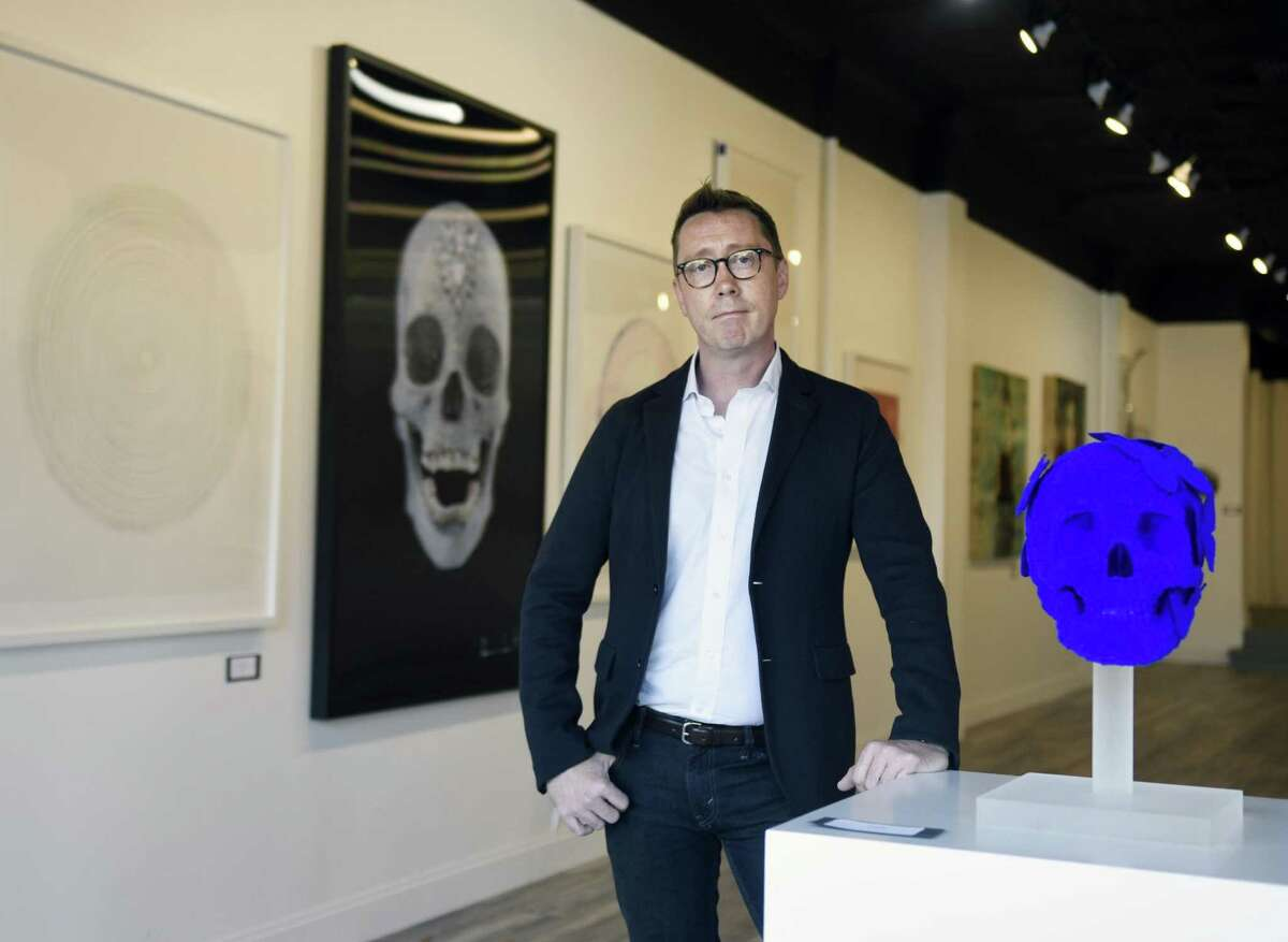 """Curator Donald Wood-Smith stands by Stephen Wilson's 2017 skull sculpture """"Adrian"""" as work by Damien Hirst is displayed behind him at VW Contemporary in Greenwich, Conn. Wednesday, Oct. 18, 2017. Located at 353 Greenwich Ave., the contemporary art gallery features work the most respected modern artists, including Koons and Hirst, at a reasonable price point."""