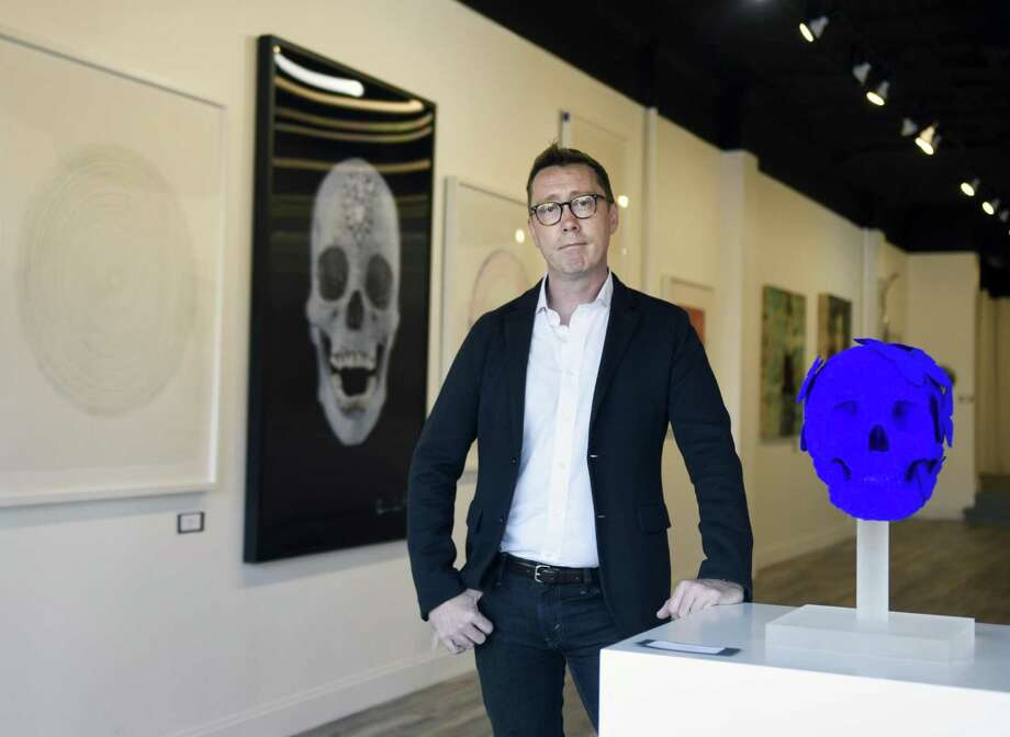 "Curator Donald Wood-Smith stands by Stephen Wilson's 2017 skull sculpture ""Adrian"" as work by Damien Hirst is displayed behind him at VW Contemporary in Greenwich, Conn. Wednesday, Oct. 18, 2017. Located at 353 Greenwich Ave., the contemporary art gallery features work the most respected modern artists, including Koons and Hirst, at a reasonable price point. Photo: Tyler Sizemore / Hearst Connecticut Media / Greenwich Time"