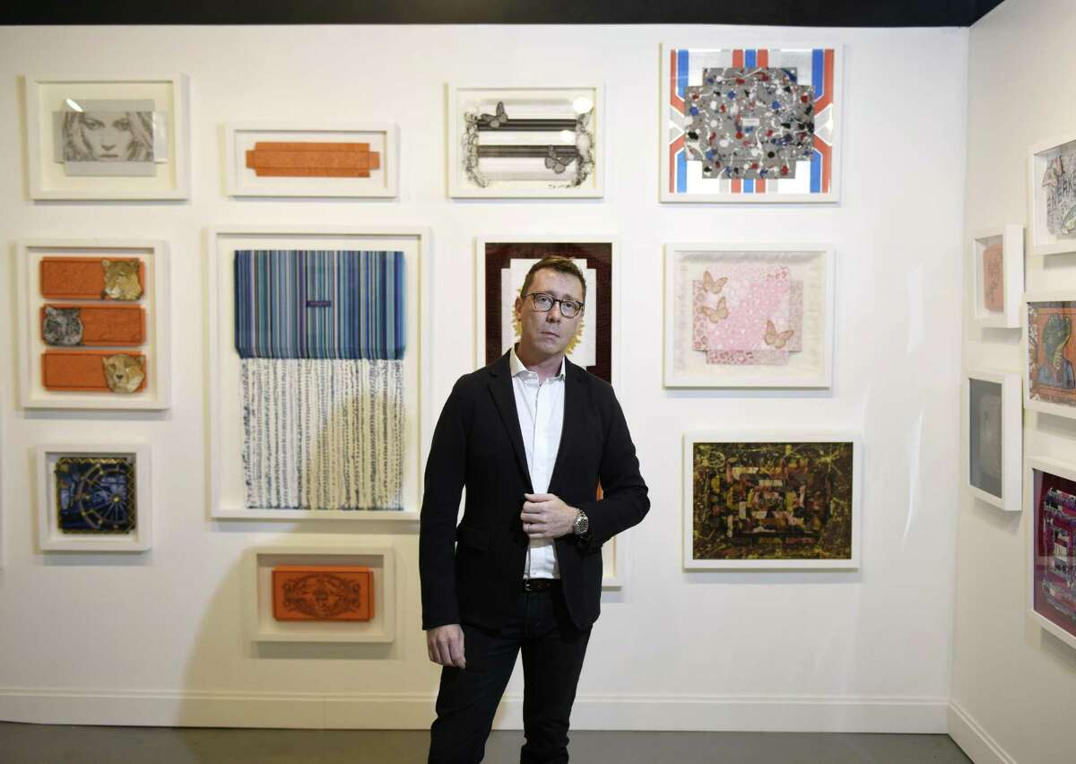 Curator Donald Wood-Smith poses in front of work from Stephen Wilson's Luxury Series at VW Contemporary in Greenwich, Conn. Wednesday, Oct. 18, 2017. Located at 353 Greenwich Ave., the contemporary art gallery features work the most respected modern artists, including Koons and Hirst, at a reasonable price point.