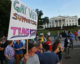 """(FILES) This file photo taken on July 26, 2017 shows protesters gathering in front of the White House in Washington, DC. A US judge on October 30, 2017 blocked US President Donald Trump's ban on transgenders serving in the US military. US District Judge Colleen Kollar-Kotelly ordered the government to """"revert to the status quo"""" that was in effect before Trump's June 30 executive order banning transgenders from serving in the military. At the same time, however, she dismissed the plaintiffs' motion to block a ban on funding for sex reassignment surgery.  / AFP PHOTO / PAUL J. RICHARDSPAUL J. RICHARDS/AFP/Getty Images"""