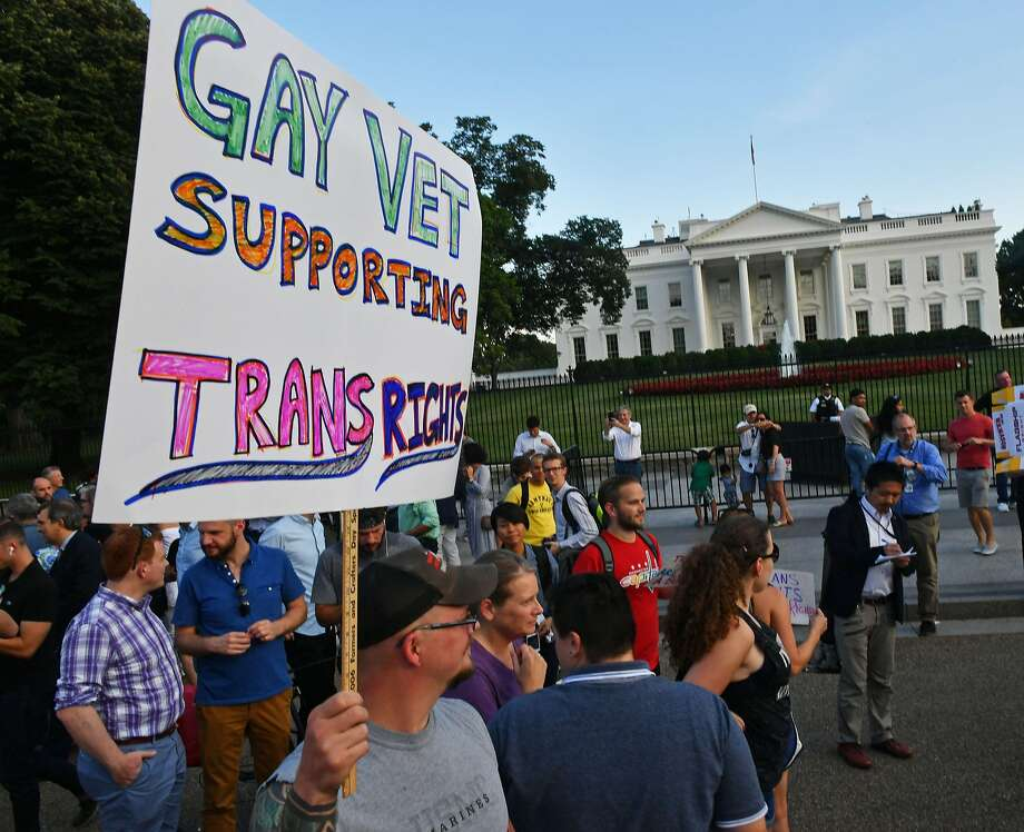 """Protesters gathering in front of the White House in Washington, DC. A US judge on October 30, 2017 blocked US President Donald Trump's ban on transgenders serving in the US military. US District Judge Colleen Kollar-Kotelly ordered the government to """"revert to the status quo"""" that was in effect before Trump's June 30 executive order banning transgenders from serving in the military. At the same time, however, she dismissed the plaintiffs' motion to block a ban on funding for sex reassignment surgery. Photo: PAUL J. RICHARDS, AFP/Getty Images"""