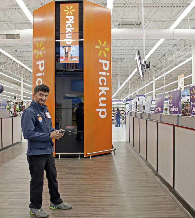 Sugar Land Wal-Mart associate Uzair Khan stands with the store's newly debuted Pickup Tower, which is designed to help busy customers save time. Photo: Kristi Nix / Houston Chronicle