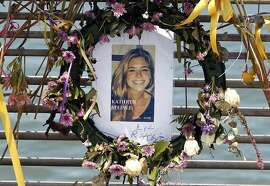 FILE - This July 17, 2015, file photo shows flowers and a portrait of Kate Steinle displayed at a memorial site on Pier 14 in San Francisco, Calif. The bullet that killed Kate Steinle two years ago ricocheted off the ground about 100 yards away before hitting her in the back and later launching a criminal case at the center of a national immigration debate. A San Francisco police officer who helped supervise the investigation testified about the bullet's trajectory Monday, Oct. 30, 2017 at Zarate's trial. (Paul Chinn /San Francisco Chronicle via AP, File)