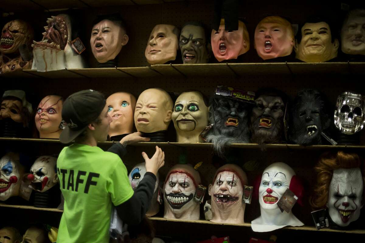 An employee places a mask back on a shelf after a customer tried it on Monday, Oct. 30, 2017 at The Halloween Store. (Katy Kildee/kkildee@mdn.net)