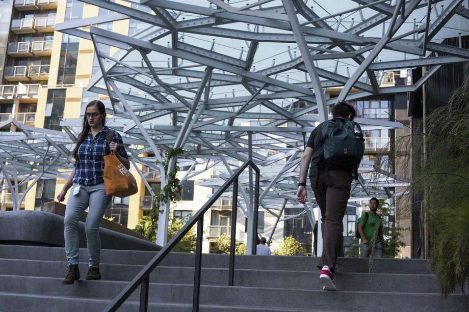People walk next to the Day 1 building at the Amazon headquarters in Seattle. Texas cities are among those bidding for a second headquarters for the firm. Voter ID, gerrymandering and anti-sanctuary cities laws should compel Amazon to stay away. Photo: David Ryder /For The Washington Post / David Ryder