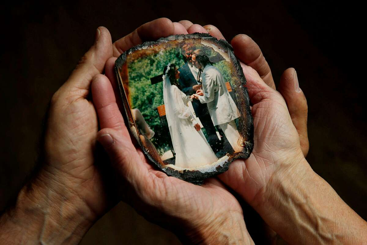 Fred Hulac and Susi Hulac hold their 1984 wedding photo, singed around the edges on Friday, Oct. 27, 2017, in Petaluma, Calif. The wedding photo is charred at the corners, but survived the Tubbs Fire. It was found in a goat field, miles away from the Hulac's Coffey Park home.