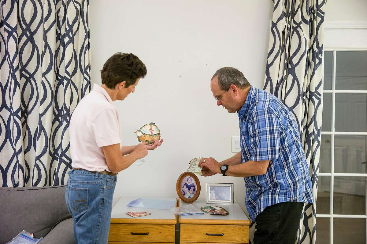 From left: Susi Hulac and her husband Fred Hulac view their damaged family photos on Friday, Oct. 27, 2017, in Petaluma, Calif. Many of the photos are charred in the corners, from the Tubbs Fire, but are still intact. Their Santa Rosa home was destroyed and are staying in a friend's house in Petaluma. Stephanie Hamilton-Oravetz found their photos and she now spends a lot of time online working to connect people to their lost items.