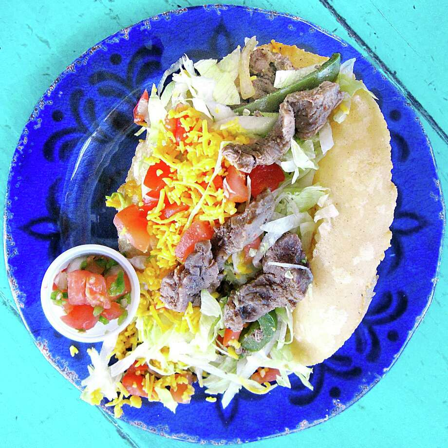 Beef fajita puffy taco with peppers, onions, lettuce, tomatoes and cheese on a handmade masa shell from Taco House. Photo: Mike Sutter /San Antonio Express-News
