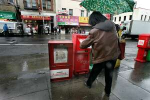 """A woman picks up a newspaper from a box nexxt to an Asian Week newspaper box on Stockton Street near Pacific in Chinatown. Asian Week ran a column titled """"Why I Hate Blacks"""".  Photographed  on Feb. 26, 2007 .  Photo by Liz Mangelsdorf/ San Francisco Chronicle"""