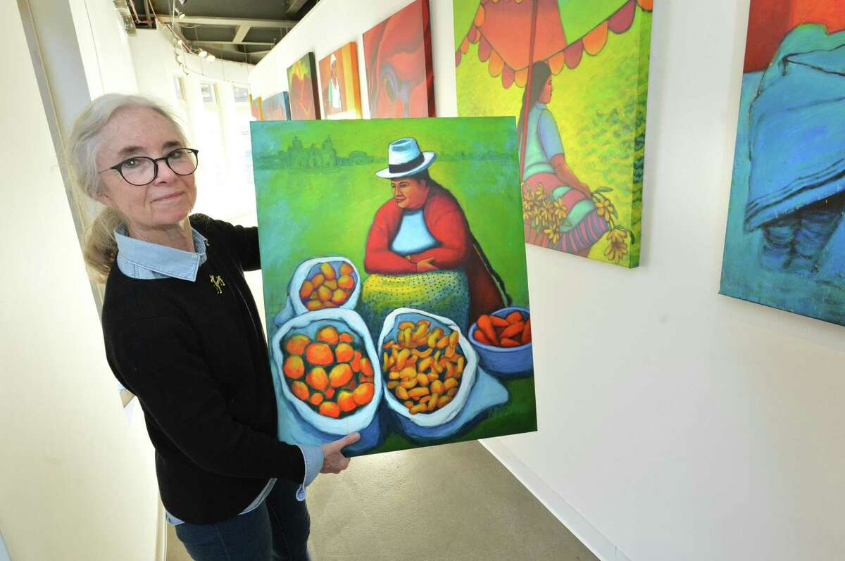 Artist Erin Nazzaro holds 'Market Day' just one of the paintings she has in the current exhibit of her works, Down to Earth at the Sidewalk Gallery in South Norwalk Conn. on Monday October 30, 2017